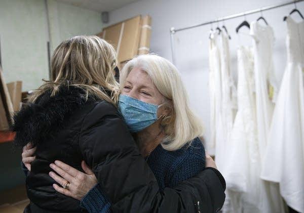 Two women hug.