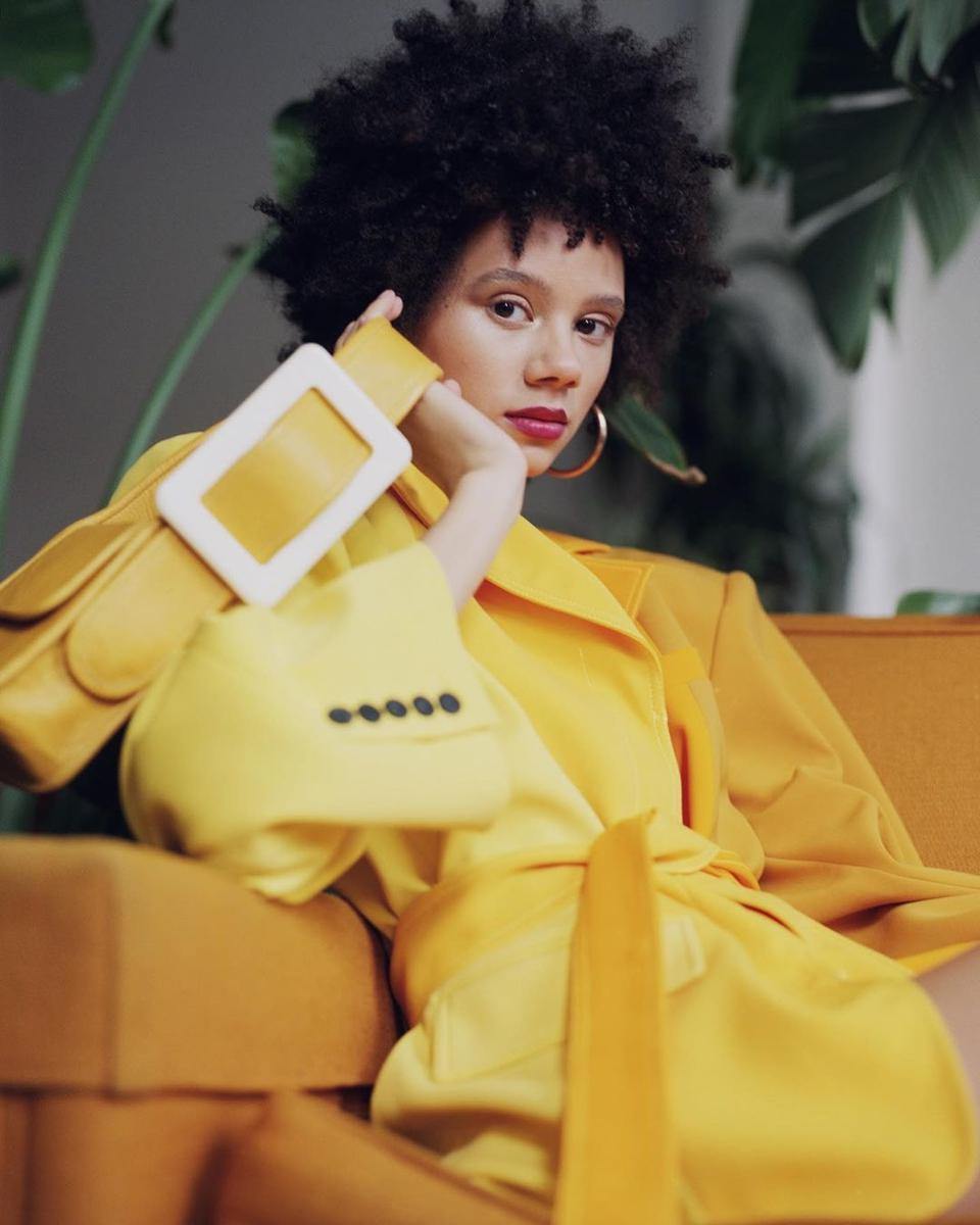 Edas model in yellow siky blazer coat with yellow Edas bag with large white buckle.
