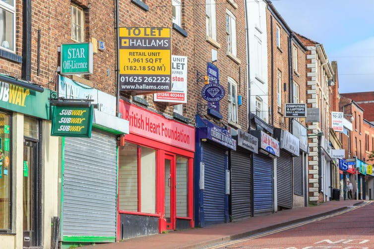 Closed storefronts and to let signs on high street
