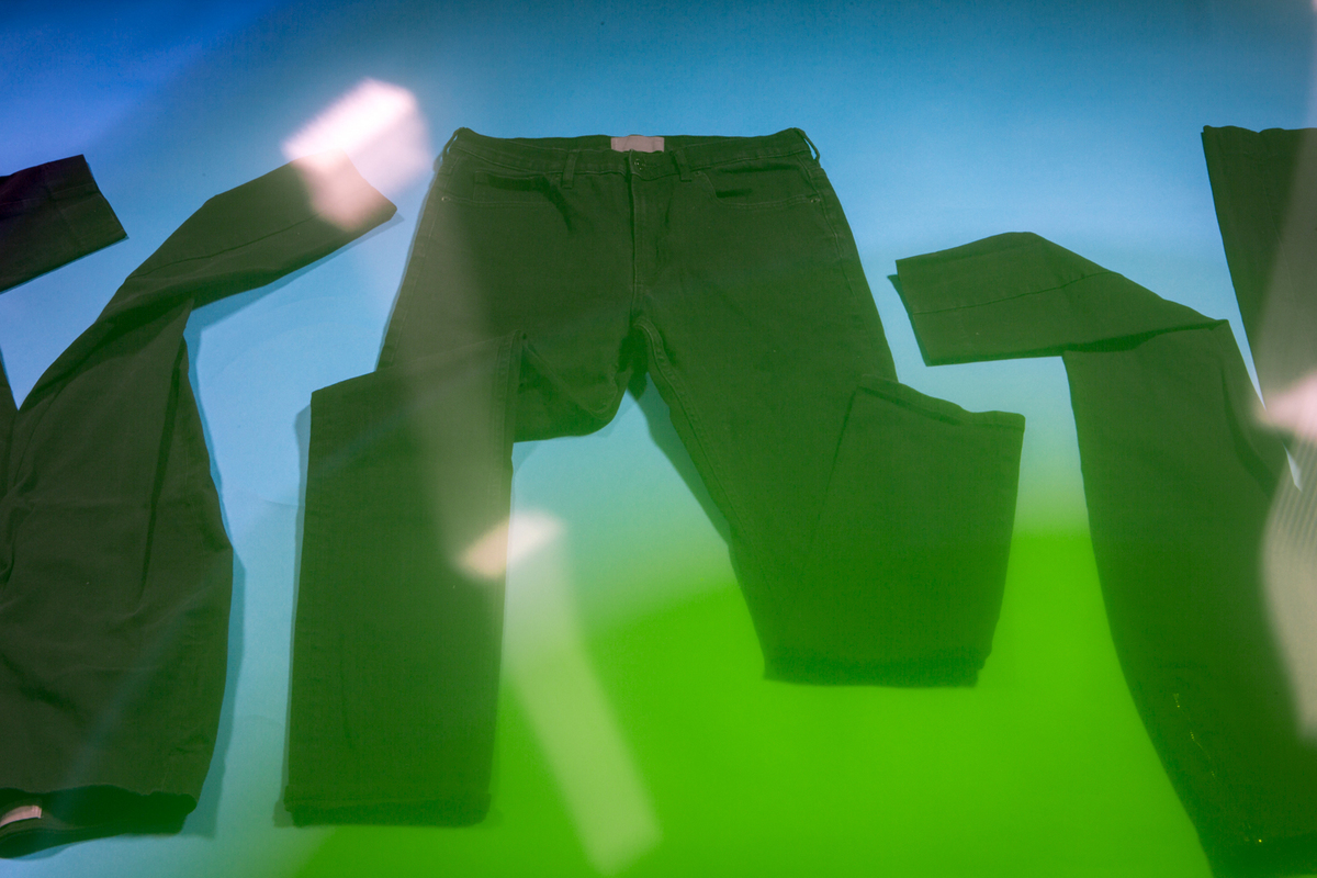 Three pairs of black pants are arranged topsy turvy on a blue backdrop with a green gradient coming over them from the bottom right corner of the frame.