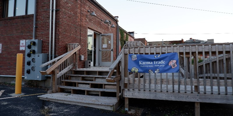 A wooden deck with stairs leading up to a large platform. It is behind a red brick building. A blue sign that says Karma Trade hangs on the side of the deck. Photo provided by Karma Trade.