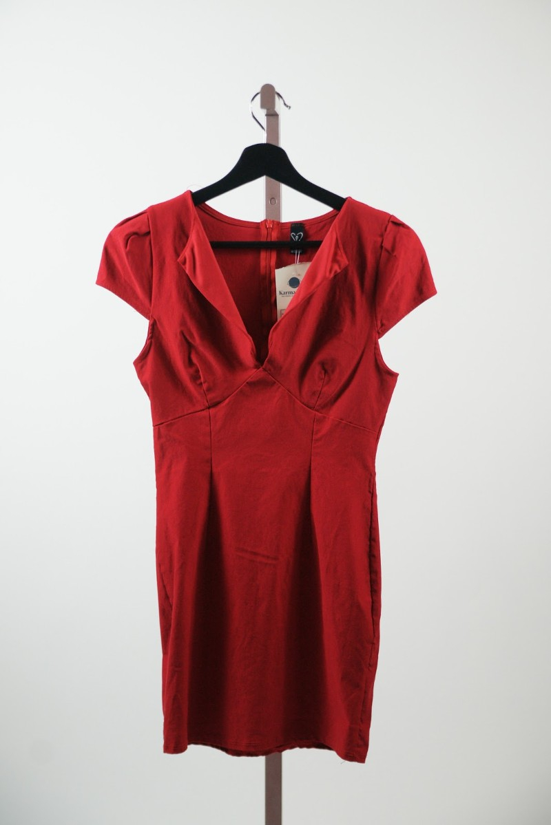 A red dress on a black hanger hangs on a pole. Photo provided by Karma Trade.