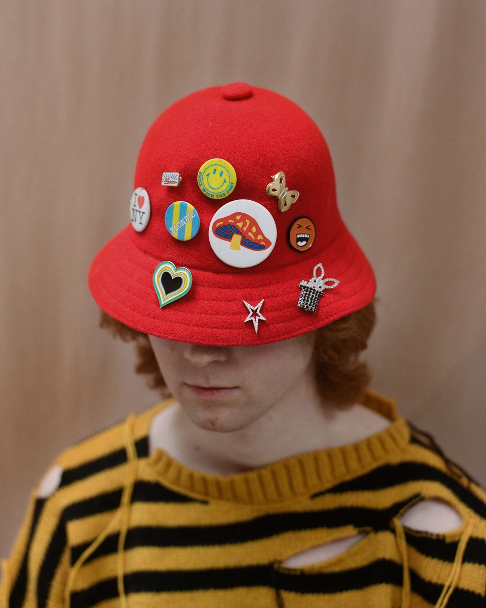 SweaterCharles Jeffrey Loverboy, HatKangol, (from left to right) I heart NY pinTHE RUSTY PIN, Small enamel pinVISVIM from MR PORTER, Yellow smiley face pinTHE RUSTY PIN, Butterfly broochCONTEMPORARY WARDROBE, Orange smiley face pin DUO LTD, Blondie pinTHE RUSTY PIN, Mushroom pinTHE RUSTY PIN, Heart pinCONTEMPORARY WARDROBE, Star EarringALAN CROCETTI, Rabbit in a hat broochART SCHOOL from MATCHES UK