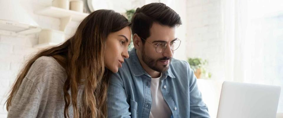 Focused young couple calculating bills, discussing planning budget together at kitchen table