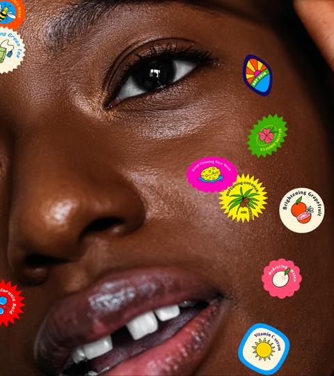 woman looking in the mirror with fruit stickers on her face