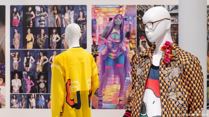 Two mannequins in colorful clothes, photos of various models in the background.